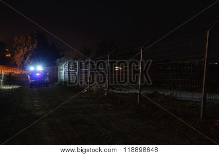 Security patrol car moving  along the fence, at night