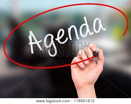 Man Hand Writing Agenda With Marker On Transparent Wipe Board