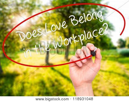 Man Hand Writing Does Love Belong In The Workplace? With Black Marker On Visual Screen