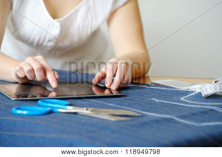 Tailoring Of Natural Wool. Woman Tailors Using Tablet.