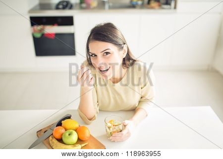 Healthy looking cheerful woman eating homemade organic fruit mix salad.Fruit diet