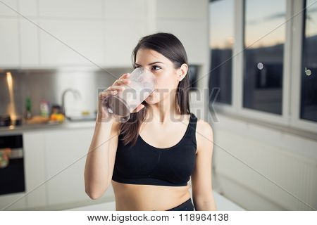 Woman drinking banana chocolate protein powder milkshake smoothie.Drinking dissolved protein powder