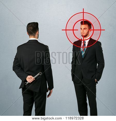 Ruthless businessman handshake with a hiding weapon and a head target point