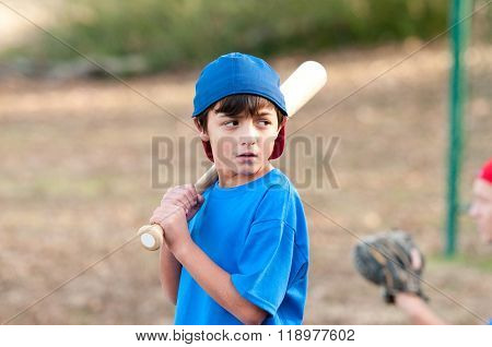 Portrait Of Serious Baseball Boy With Wooden Bat