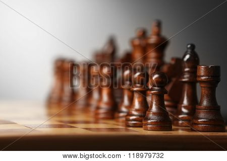 Chess pieces and game board on grey blurred background