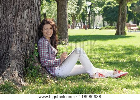 Girl Sitting In The Park On The Grass And Draws.