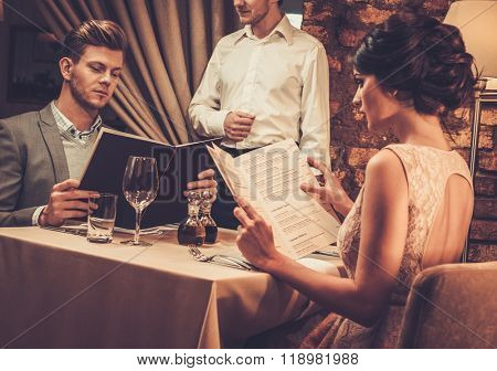 Waiter explaining the menu to stylish wealthy couple in restaurant.