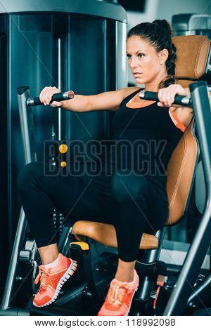 Female Athlete Exercising On Chest Press