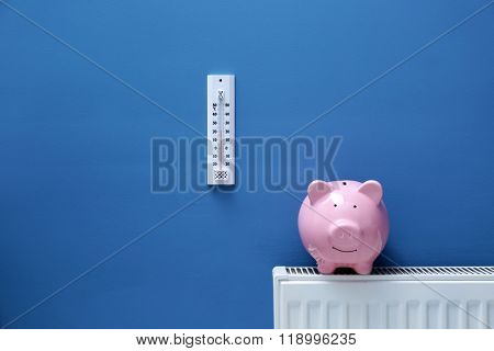 Piggy bank on radiator with thermometer. Saving  heating in winter