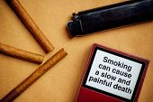 Smoking cigarettes addiction and health issue concept flat lay arrangement smoking can cause a slow and painful death generic message on a pack of cigarettes. poster
