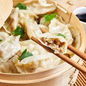 Steamed asian dumplings. Dumplings with fillings in a bamboo steamer poster