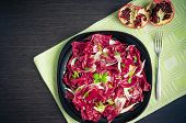 Easy diet chicory salad with pomegranate on dark wooden background with fork. Italian bitter red chicory radicchio salad. Vegetarian Food. Healthy food. Dietary meal. Top view copy space horizontal poster