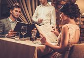 Waiter explaining the menu to stylish wealthy couple in restaurant. poster