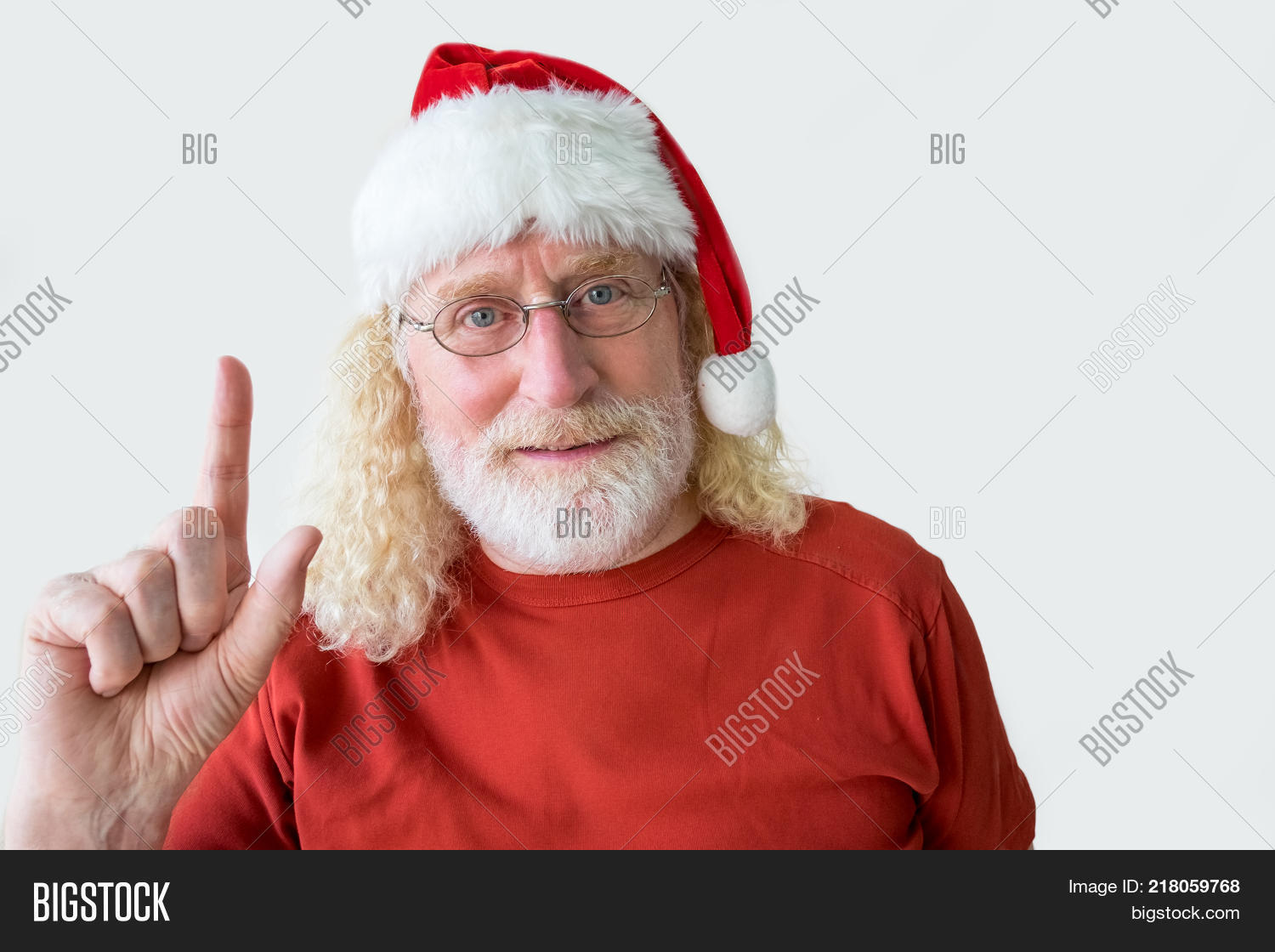 f09f8d1ba37 Studio shot of senior man in Christmas hat. Aged positive man raising  finger and looking