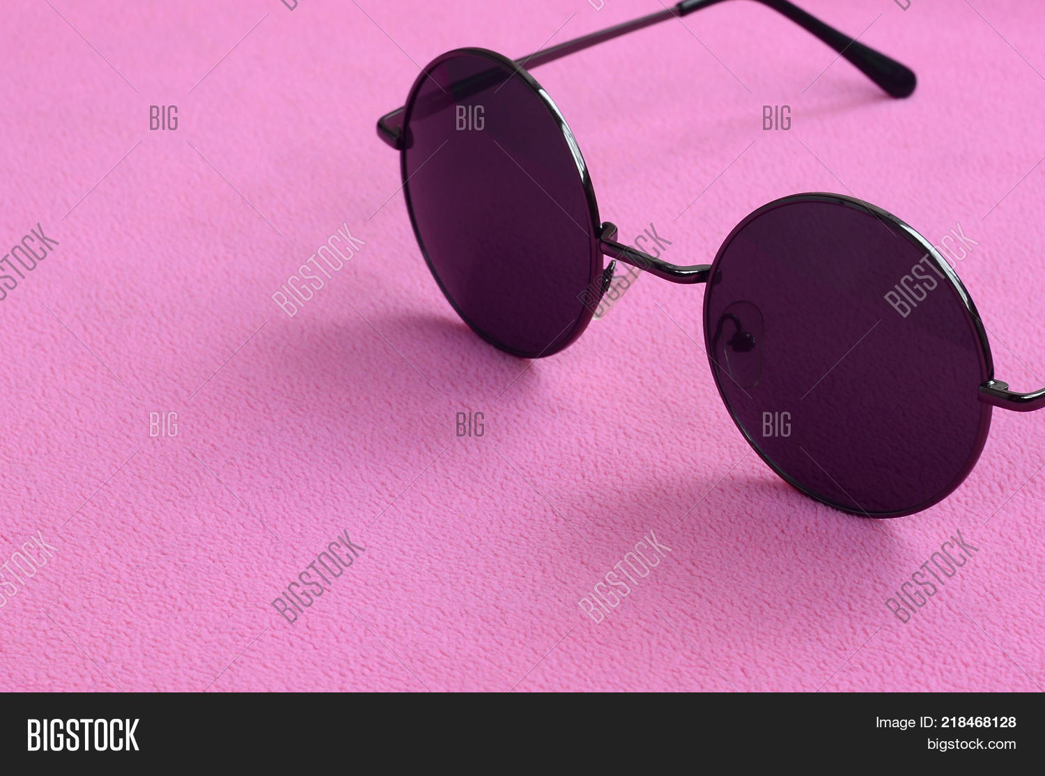 77abdd13a27e Stylish black sunglasses with round glasses lies on a blanket made of soft  and fluffy light