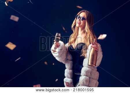 Well-dressed pretty woman in sunglasses holding champagne, smiling and standing in falling confetti.