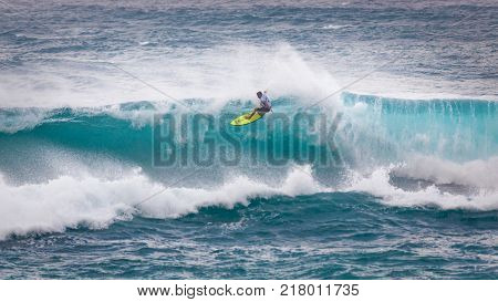 SUNSET BEACH HAWAII USA - DECEMBER 2, 2017: Surfer competing at the 2017 Vans World Cup of Surfing competition at Sunset Beach on Oahu's scenic North Shore. This is the second of three surfing competitions and Conner Coffin took first place.