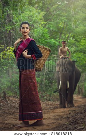 Beautiful model in traditional suit with mahout riding the elephant in the deep forest background
