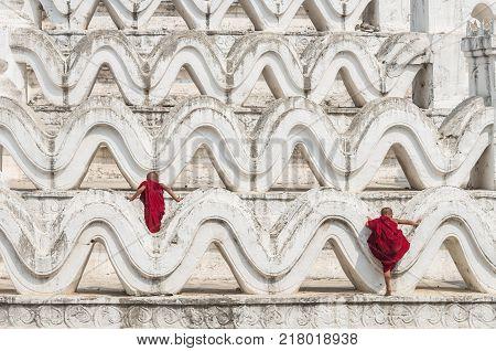 Two young monk are Clambering on the Mya Thein Tan Pagoda at bagan mandalay myanmar