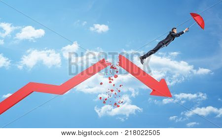 A small businessman holds a red umbrella and flies away from a large red statistic arrow broken in half. Down economy. Exit falling market. Avoid money loss.
