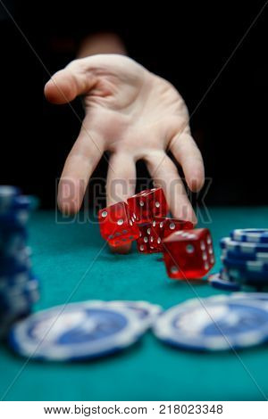 Image of man throwing red dices on table with chips in casino,