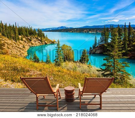 Two comfortable wooden deckchairs by the Abraham lake. Warm September in the mountains of Canada. Concept of ecological and active tourism