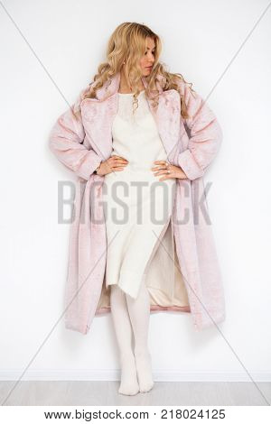 Blonde woman in pink fur coat, full length portrait isolated on white wall