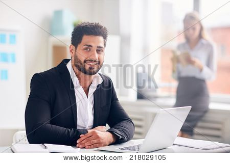 Smiling businessman in suit looking at camera while working over new online project in office