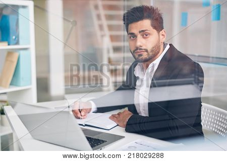Businessman writing agenda in his notebook while working in office