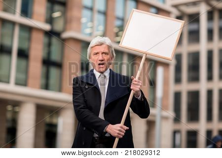 Dissatisfied man with protest placard shouting out his attitude towards business unjustice or discrimination
