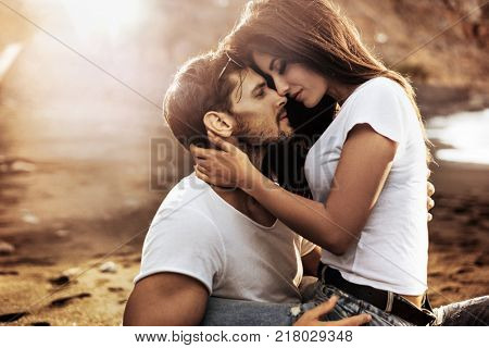 Handsome man hugging his woman on a beach
