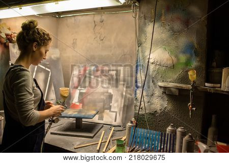 Young creative female with airbrush gun making grunge pictures in workshop