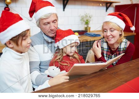 Family in Santa caps reading book of xmas tales by table on festive evening
