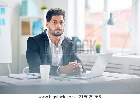 Calm businessman sitting in front of laptop by his workplace in office