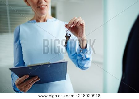 Mature realtor with clipboard giving key from office to new tenant