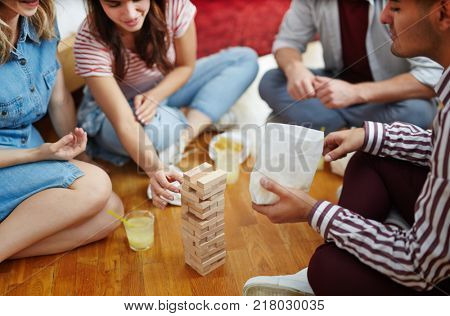 One of girls taking out wooden brick from construction on the floor at leisure