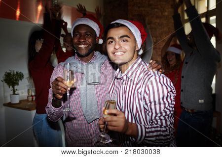 Two intercultural guys holding flutes with champagne while enjoying Christmas party