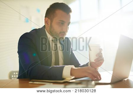 Businessman with drink searching for curious data in the net in office