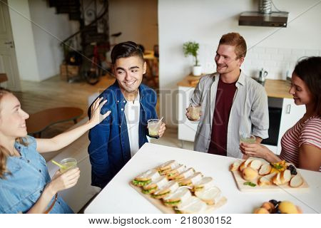 Attractive young man with drink looking at one of girls during talk at party