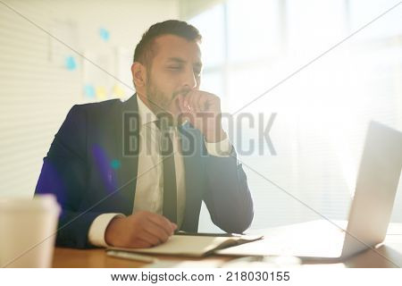 Yawning businessman in suit sitting in front of laptop and networking in office
