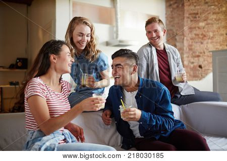 Young joyful companions discussing funny things while having drinks at home party