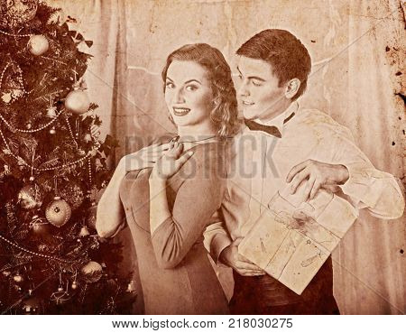 Christmas nostalgy couple on party near Xmas tree take gift box. Happy family on holiday. Vintage sepia old retro photo 1910-1940.