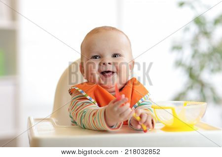 happy baby boy with spoon at table in nursery