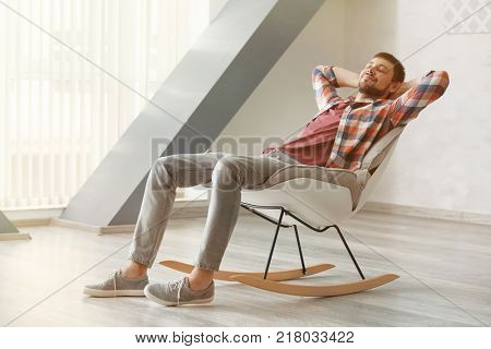 Handsome man relaxing in rocking-chair at home