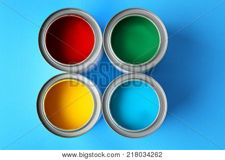 Multicolored paint in tin cans on color background, top view