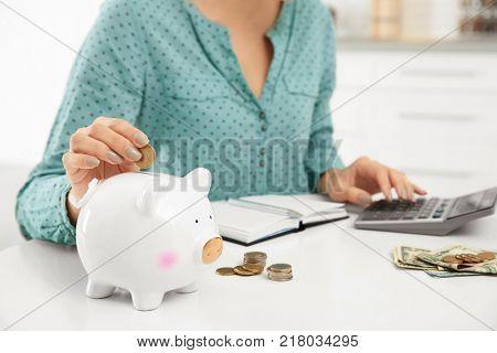 Woman putting coin into piggy bank, closeup