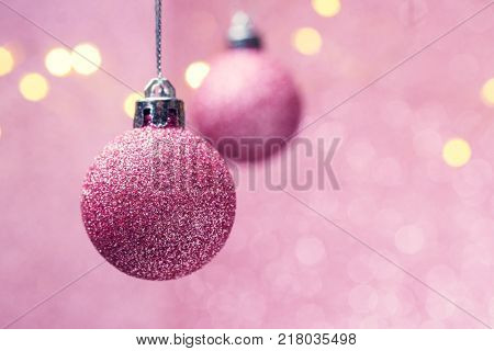 Image of two Christmas pink balls on pink background with spots.