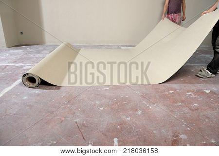 Manual workers laying vinyl on floor.