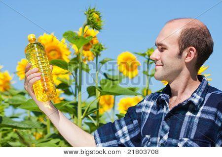 Farmer Holding Bottle Of Sunflowers Oil