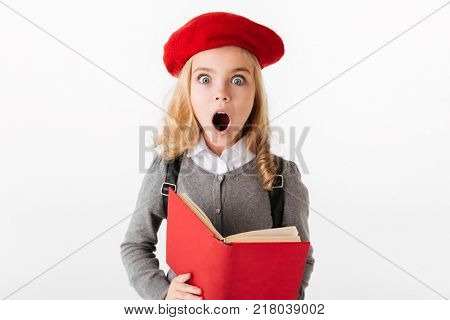 Portrait of a shocked little schoolgirl dressed in uniform holding book and looking at camera isolated over white background